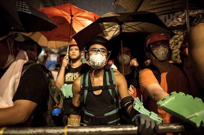 HONG KONG - OCTOBER 19:  Pro-democracy protesters hold umbrellas in the rain in front of barricades during a standoff with police at Mongkok district on October 19, 2014 in Hong Kong. Police have begun to take measures to remove the blockades put in place by pro-democracy supporters following weeks of protests. Hong Kong's Chief Executive Leung Chun-ying today called for talks to resume between protest groups and government officials and said his government is ready to meet with student leaders to discuss 'universal suffrage'  (Photo by Hok Chun Kwan/Getty Images)